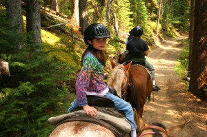 Young girl horse back riding on forest trail.